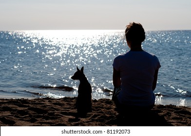 Girl silhouette sitting on the beach with a small dog