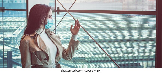 Girl in silohuette with medical mask is staying inside a modern building and look out of the window during pandemic of Coronavirus Covid-19