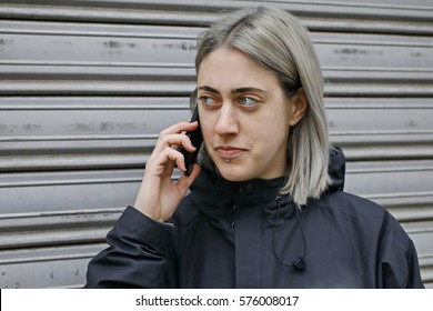 girl with silver hair dressed in black talking on the phone