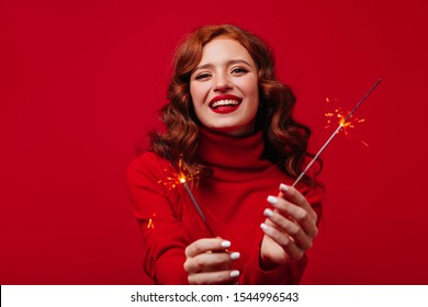 Girl with sincere smile looks into camera, posing with burning Christmas sparklers. Portrait of redhead lady in red sweater on isolated background