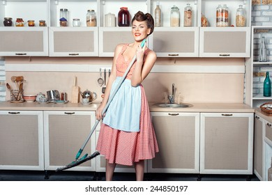 Girl singing in the kitchen, in the hands holding a mop which makes cleaning.