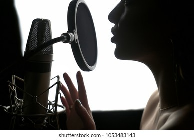 Girl singing to the microphone in a studio. Female vocal. Black and White.