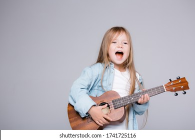 The girl sings and plays the ukulele. The child laughs, poses for the camera and enjoys the music. Learning to play ukuleles.