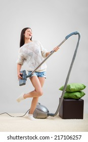 Girl sings while she tidies up the room with the vacuum cleaner