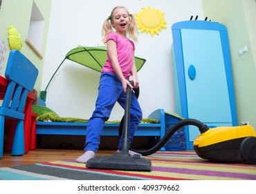 Girl sings while she tidies up the room with vacuum cleaner , girl cleaning floor with hoover