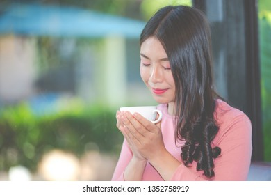 The girl is sipping coffee with pleasure at the coffee shop.