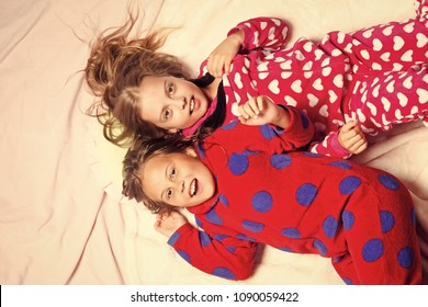 Girl sisters in pajamas happy smile in bed, top view. Children nightwear fashion. Bedtime, slumber, dream, sleepover. Childhood, family, love, friendship. Comfort, home concept.