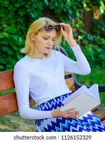 Girl sit bench relaxing with book, green nature background. Reading literature as hobby. Girl keen on book keep reading. Woman blonde take break relaxing in park reading book. Ultimate best book list.