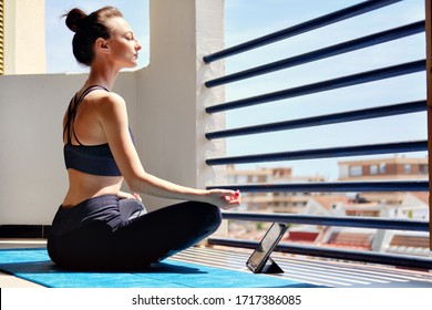 Girl sit cross-legged on mat do meditation practice at home in terrace sunny warm day view. Use tablet device listen calm music in state in deep relaxation, application user modern tech yoga concept