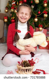 Girl sit near christmas fir tree and playing with bear, christmas decoration at home, happy emotion, winter holiday concept
