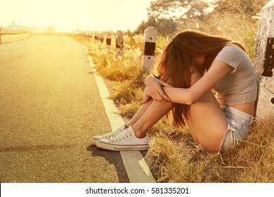 Girl sit on the road alone crestfallen and sad at sunset time.