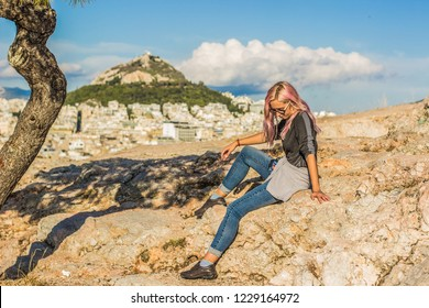 girl sit on stones on big city background with lonely mountain and looking side ways