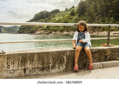Girl sit in the wall. Nature landscape background. Asturias. Spain