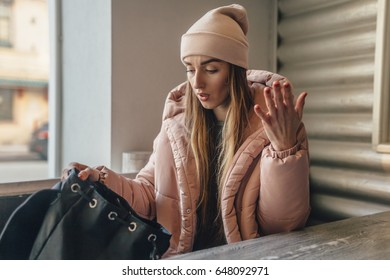 The girl sits in cafe in the winter. On her a pink cap and a jacket. The girl is revolted because she can't find something in the black briefcase.