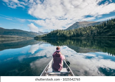 A girl sits in a canoe in a mirroring lake during in Alaska