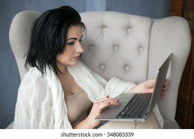 A girl sits in a chair under a blanket and works in the home atmosphere.