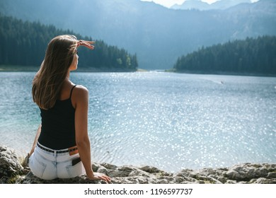 girl sits and looks at the black lake