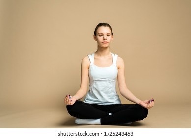 A girl sits in a lotus position and meditates with her eyes closed. Zen practice, breath technique. Consideration and praying