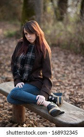A girl sits on a bench outside during autumn season, staring into the camera.