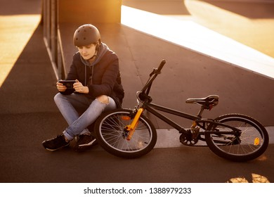 girl sits on the bike stand on the asphalt in the helmet on the sunset