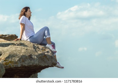 A girl sits on the edge of a stone mountain, over an abyss