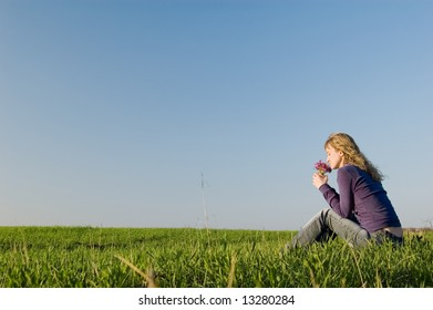 Girl sits on a grass and smells a bunch of flowers