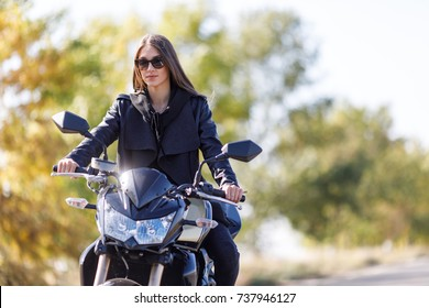 A girl sits on a motorcycle in black leather clothes