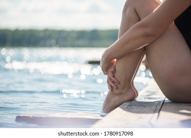 The girl sits on an old wooden pier on the lake and sunbathes.
