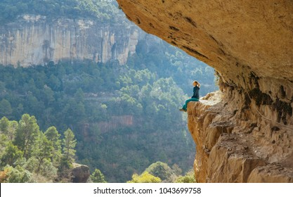 The girl sits on a picturesque ledge of a rock. Beautiful view. Siurana. Spain. The girl on the cliff. Extreme. Rock climbing. Rest in spainii.vysota. Danger. Extreme.