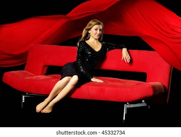 Girl  sits on a red sofa