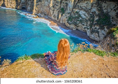 The girl sits on the rock and looks at the beautiful blue sea in the center of Beirut, Lebanon. Dress with a geometrical print. The girl with orange hair on Pigeon's rock