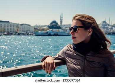 The girl sits on the ship and looks at the sea