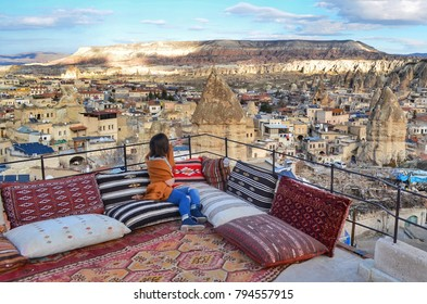 The girl sits on soft cushions on the open veranda and looks at the panorama of the city of Goreme, Cappadocia, Turkey