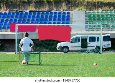 A girl sits on a sports field in front of a football goal. Nearby lies the ball