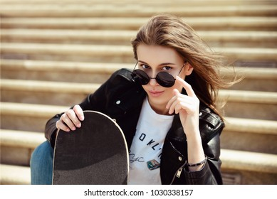 The girl sits on the steps in a leather jacket and with a skateboard in her hands.