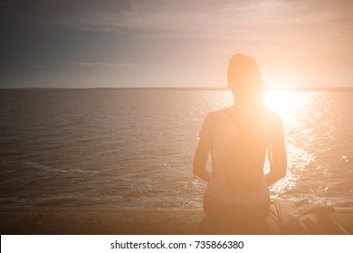 Girl sits on the stone embankment of coast sea and looks at the sun reflects on the surface of the water. Backlight sunbeam light. Concept theme: travel, meditation, contemplation, relax, quiet