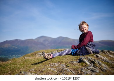A girl sits on the summit of Cat Bells, a mountain in the Lake District National Park, Cumbria, UK during a clear, sunny day with Skiddaw summit in the background.