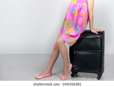 The girl sits on a travel bag. Travel.