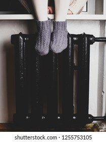 A girl sits on a windowsill put their feet in knitted woolen socks on the radiator and heated on a cold winter evening.