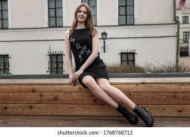 A girl sits on a wooden bench in the street and looks at the camera. a Girl sits on a wooden surface and looks at the camera. a Girl looks at the camera. portrait of a girl in a black dress