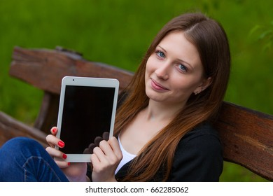 A girl sits on a wooden bench looking at a tablet computer