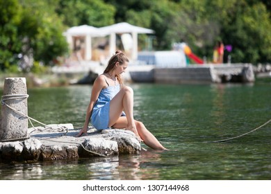girl sits on a wooden pier and soaks her feet in the water. Summer Sunny day by the sea. Vacation and travel concept