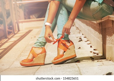 girl sits and orange bow tying on their sandals