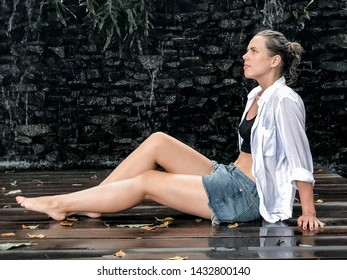 The girl sits in shorts at the waterfall
