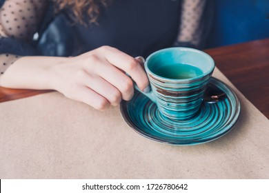 A girl sits at a table covered with Kraft paper and her hand touches a striped cup of espresso. Copyspace on the right.