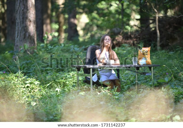 girl-sits-table-forest-eats-600w-1731142