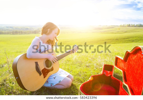 Girl sitting with acoustic guitar at field Copy space for inscription
