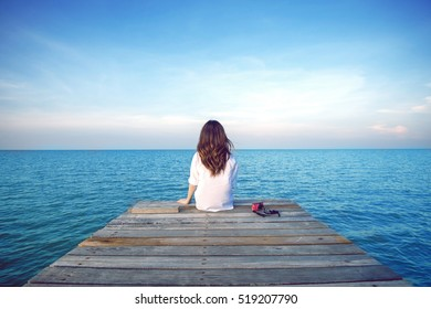 Girl sitting alone on a the wooden bridge on the sea. Vintage tone style. (frustrated depression)