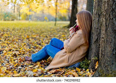 Girl sitting in the autumn park and dreaming about her life with notes concept