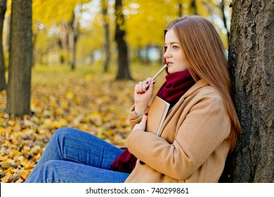 Girl sitting in the autumn park and planning her goals and ways with notes. Life coach goals concept